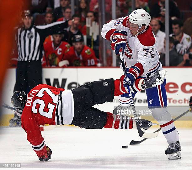 Alexei Emelin of the Montreal Canadiens hits Johnny Oduya of the Chicago Blackhawks during a preason game at the United Center on October 1 2014 in...