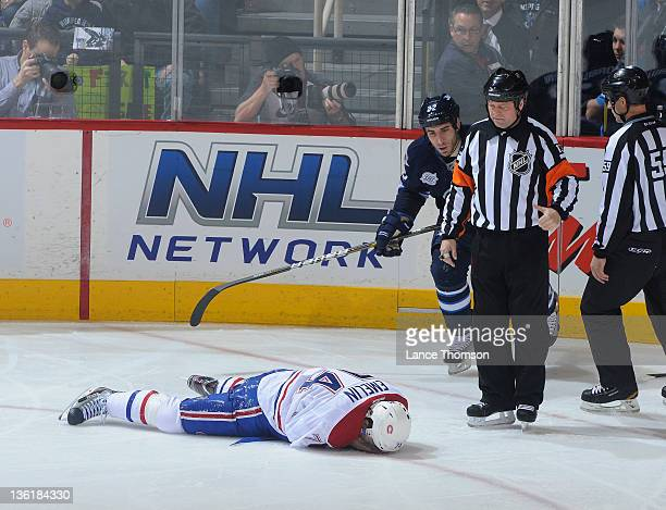 Alexei Emelin of the Montreal Canadiens lays on the ice as Chris Thorburn of the Winnipeg Jets referee Dan O'Halloran and linesman Steve Barton look...