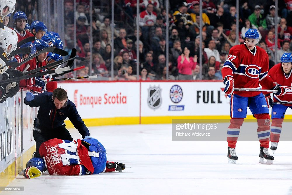Alexei Emelin #74 of the Montreal Canadiens lies on the ice after colliding with Milan Lucic #17 of the Boston Bruins (not pictured) during the NHL game at the Bell Centre on April 6, 2013 in Montreal, Quebec, Canada.