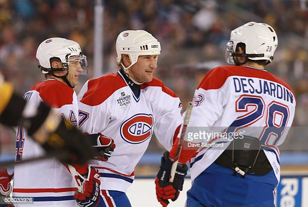 Alexei Kovalev of the Montreal Canadiens Alumni Team celebrates scoring a goal with Eric Desjardins in the first period during the Alumni Game as...