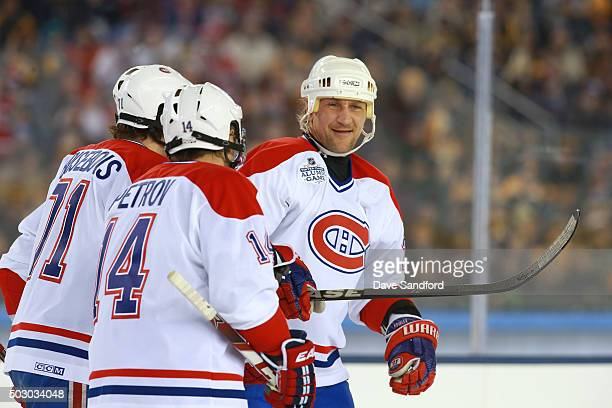 Alexei Kovalev of the Montreal Canadiens Alumni Team celebrates scoring a goal with Oleg Petrov and Patrice Brisebois in the first period during the...