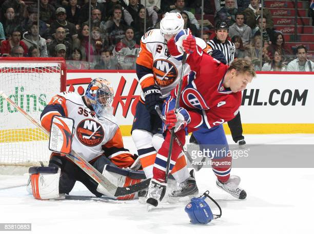 Alexei Kovalev of the Montreal Canadiens attempts a backhand shot on Joey MacDonald of the New York Islanders after having his helmet knocked off his...