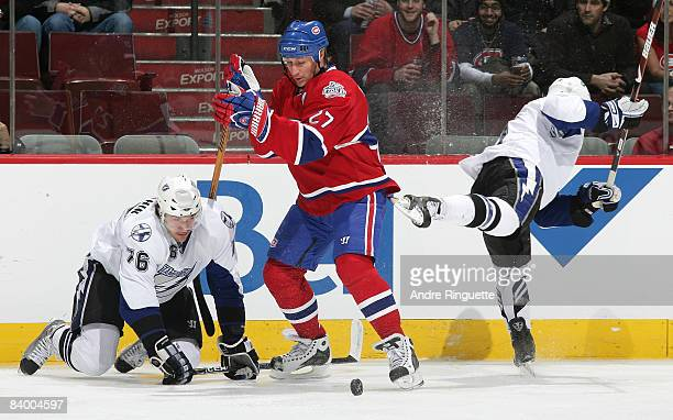 Alexei Kovalev of the Montreal Canadiens avoids a check by Steve Downie of the Tampa Bay Lightning and controls the puck against Evgeny Artyukhin of...