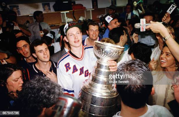 Alexei Kovalev of the New York Rangers holds the Stanley Cup Trophy in the locker room after the Rangers defeated the Vancouver Canucks in Game 7 of...