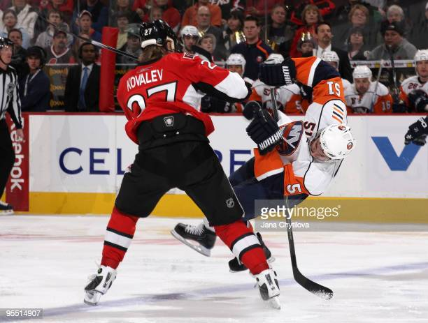 Alexei Kovalev of the Ottawa Senators checks Frans Nielsen the New York Islanders at Scotiabank Place on December 31 2009 in Ottawa Ontario Canada