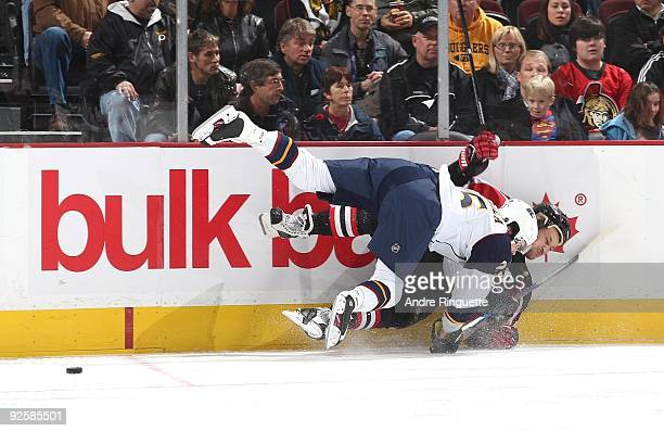Alexei Kovalev of the Ottawa Senators is bodychecked off the puck by Anssi Salmela of the Atlanta Thrashers at Scotiabank Place on October 31 2009 in...