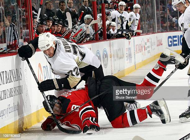 Alexei Kovalev of the Pittsburgh Penguins hits Dainius Zubrus of the New Jersey Devils to the ice at the Prudential Center on March 4 2011 in Newark...