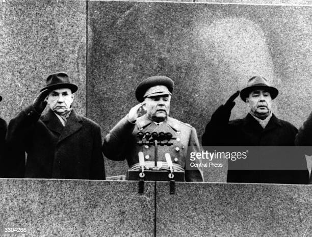 Alexei N Kosygin Soviet Premier with Rodion Y Malinovsky the Defence Minister and Leonid I Brezhnev saluting a procession pass through Moscow's Red...