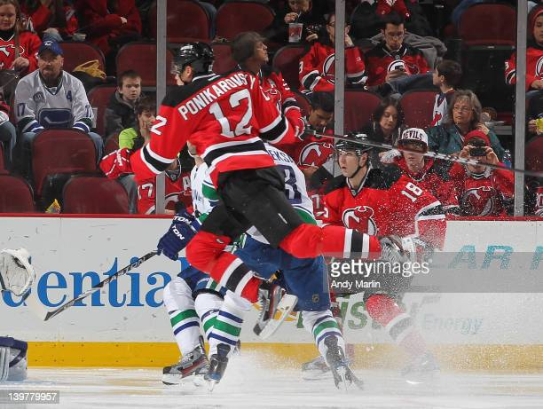 Alexei Ponikarovsky of the New Jersey Devils jumps to avoid a collision with Kevin Bieksa of the Vancouver Canucks during the game at the Prudential...