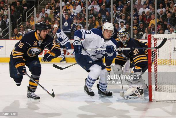 Alexei Ponikarovsky of the Toronto Maple Leafs races to the puck between Nathan Paetsch and Ryan Miller of the Buffalo Sabres on December 12, 2008 at...