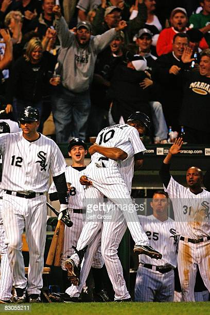Alexei Ramirez and Jermaine Dye of the Chicago White Sox celebrate at the top of the dugout with teammates after Ramirez hit a grand slam home run to...