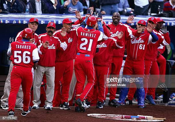 Alexei Ramirez of Team Cuba is congratulated by teammates after hitting a RBI sacrafice fly against Team Domincan Republic during the seventh inning...