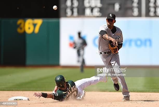 Alexei Ramirez of the Chicago White Sox completes the doubleplay over the top of Josh Donaldson of the Oakland Athletics in the bottom of the ninth...