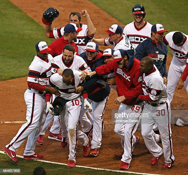 Alexei Ramirez of the Chicago White Sox is mobbed by teammates at home plate after hitting a tworun walkoff home run in the bottom of the 9th inning...