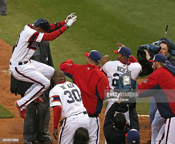 Alexei Ramirez of the Chicago White Sox jumps onto teammates at home plate after hitting a tworun walkoff home run in the bottom of the 9th inning to...