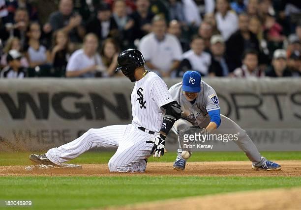 Alexei Ramirez of the Chicago White Sox slides safely into third base with a triple as third baseman Jamey Carroll of the Kansas City Royals loses...