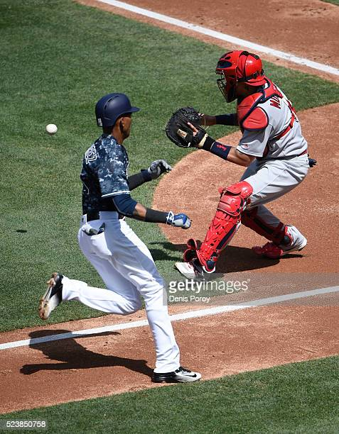 Alexei Ramirez of the San Diego Padres scores ahead of the throw to Yadier Molina of the St. Louis Cardinals during the second inning of a baseball...