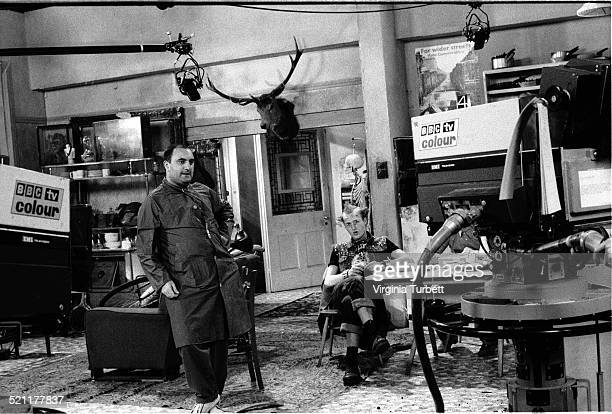 Alexei Sayle as a member of the Balowski family with Adrian Edmondson as Vyvyan behind on set in front of BBC cameras during the filming of The Young...