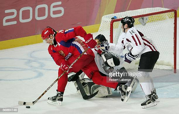 Alexei Yashin of Russia fights for the puck with Leonids Tambijevs of Latvia during the men's ice hockey Preliminary Round Group B match between...