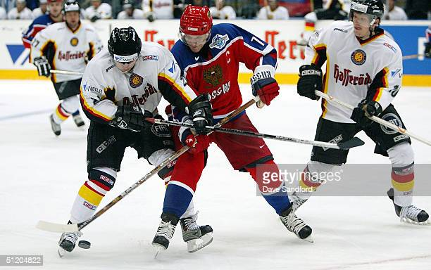 Alexei Yashin of Team Russia battles for control of the puck with Daniel Kreutzer of Team Germany during an exhibition game at Koln arena August 22,...