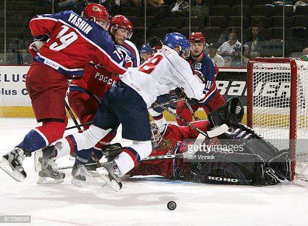 Alexei Yashin of Team Russia checks Pavol Demitra of Team Slovakia into Ilya Briyzgalov of Team Russia as they look for the rebound during the second...