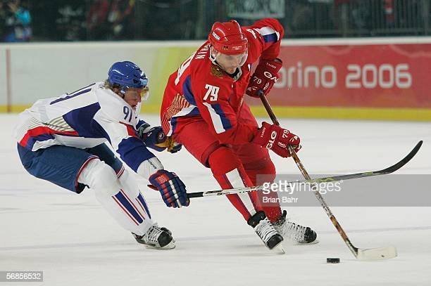 Alexei Yashin of tries to get around the defense of Marcel Hossa of Slovakia in the first period during the men's ice hockey Preliminary Round Group...