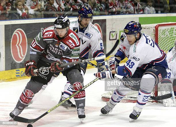 Alexej Dmitriev of Cologne and Felix Petermann of Mannheim fight for the puck in front of Dan McGills of Mannheim during the DEL PlayOff match...