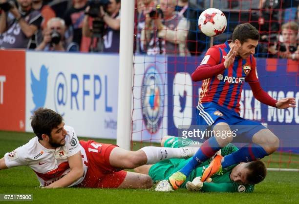 Alexey Ionov PFC CSKA Moscow vies for the ball with Georgi Dzhikiya and goalkeeper Artyom Rebrov of FC Spartak Moscow during the Russian Premier...