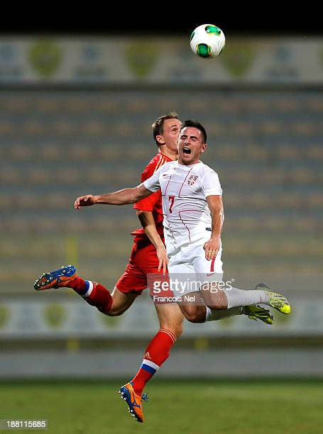 Alexey Kozlov of Russia competes for the ball with Zoran Tosic of Serbia during the International Football match between Serbia and Russia at the...