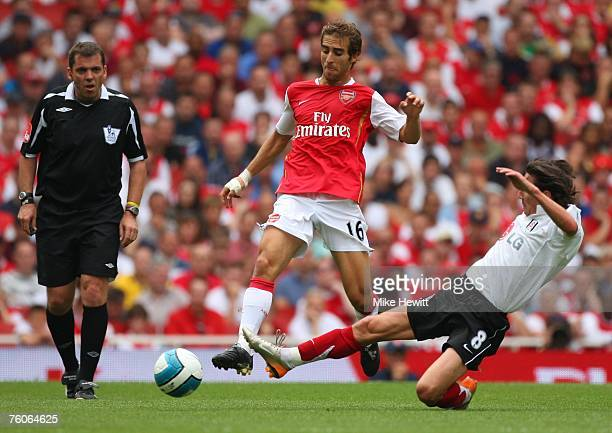 Alexey Smertin of Fulham tackles Mathieu Flamini of Arsenal in front of referee Phil Dowd during the Barclays Premier League match between Arsenal...