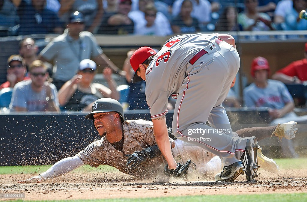 Alexi Amarista #5 of the San Diego Padres is tagged out at the plate by Homer Bailey #34 of the Cincinnati Reds during the sixth inning of a baseball game at PETCO Park on July 31, 2016 in San Diego, California.