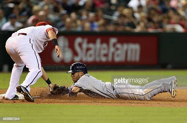 Alexi Amarista of the San Diego Padres is tagged out by infielder Jake Lamb of the Arizona Diamondbacks as he slides into third base during the third...