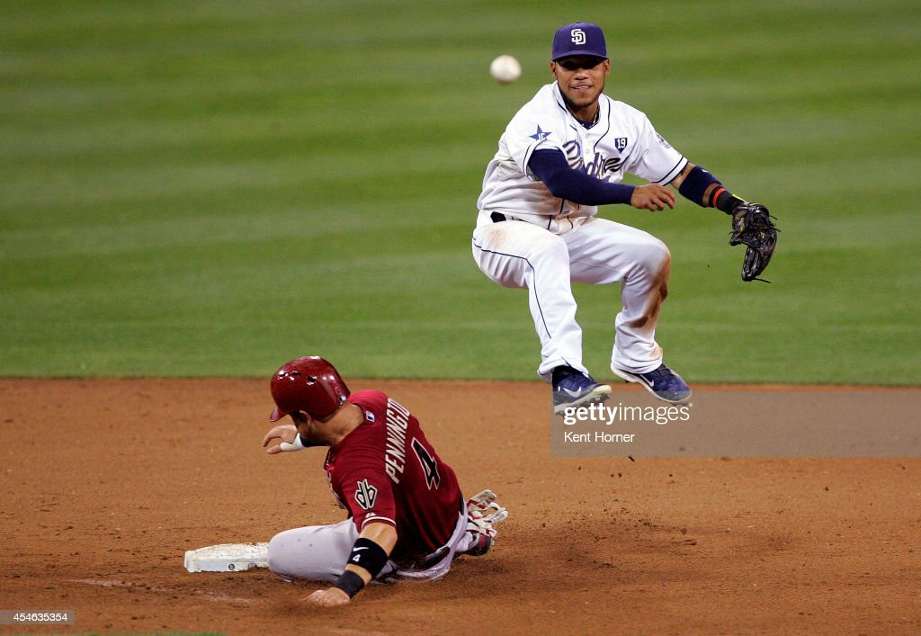 Alexi Amarista #5 of the San Diego Padres leaps into the air over Cliff Pennington #4 of the Arizona Diamondbacks while throwing to first base for the double play in the seventh inning of the game at Petco Park on September 3, 2014 in San Diego, California.