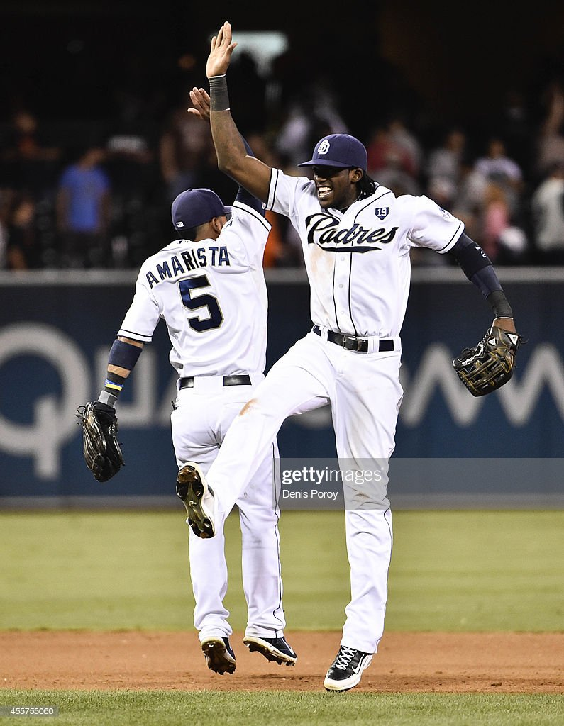 Alexi Amarista #5 of the San Diego Padres, left, and Cameron Maybin #24 celebrate after the Padres beat the San Francisco Giants 5-0 in a baseball game at Petco Park September, 19, 2014 in San Diego, California.