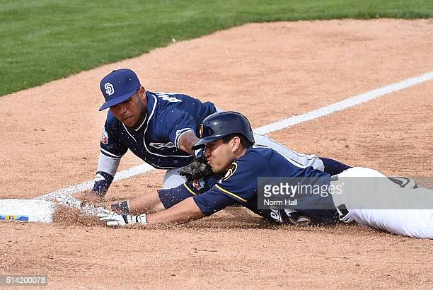 Alexi Amarista of the San Diego Padres tags out Ramon Flores of the Milwaukee Brewers at third base during the third inning of a spring training game...