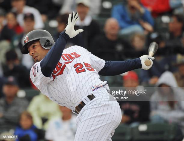 Alexi Casilla of the Minnesota Twins follows through after a hit during a Grapefruit League Spring Training Game against the Boston Red Sox at...
