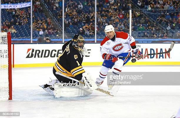 Alexie Kovalev of the Montreal Canadiens Alumni Team and goaltender Andrew Raycroft of the Boston Bruins Alumni Team look to the puck during the...