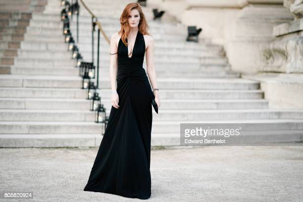 Alexina Graham wears a black dress and a black clutch outside the amfAR dinner at Petit Palais during Paris Fashion Week Haute Couture Fall/Winter...
