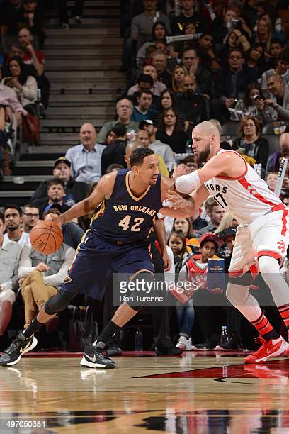 Alexis Ajinca of the New Orleans Pelicans handles the ball against Jonas Valanciunas of the Toronto Raptors on November 13 2015 at the Air Canada...