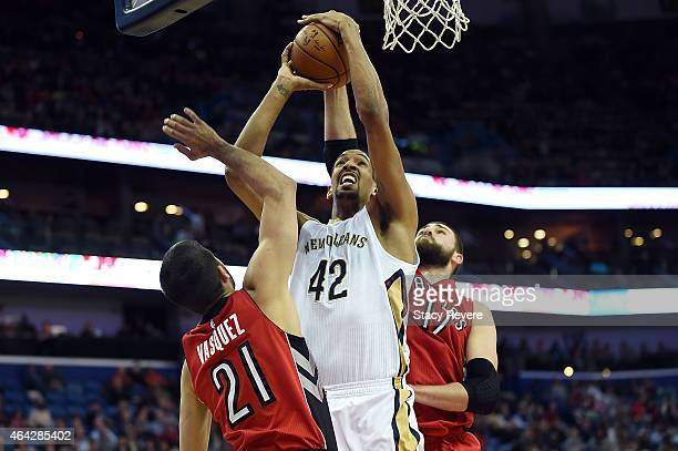 Alexis Ajinca of the New Orleans Pelicans is defended by Jonas Valanciunas and Greivis Vasquez of the Toronto Raptors during the first half of a game...