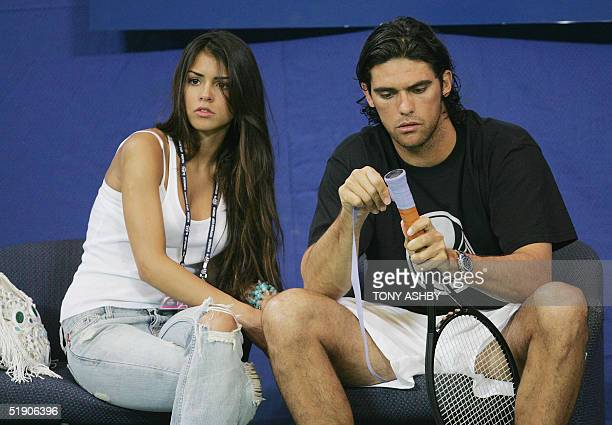 Alexis Barbara of the US, girlfriend of Australian tennis player Mark Philippoussis , sits with him as he wraps a racket grip during practice for the...