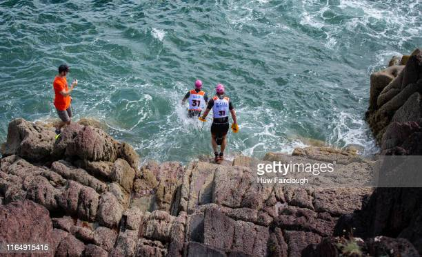 Alexis Charrier and Nicolas Remires descend the cliff to enter the sea in the Wales SwimRun race through Pembrokeshire starting in Freshwater East...
