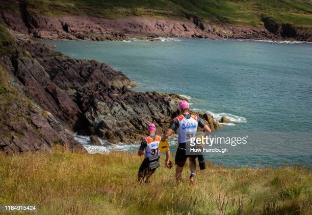 Alexis Charrier and Nicolas Remires descend the cliff to enter the sea during the Wales SwimRun race through Pembrokeshire starting in Freshwater...