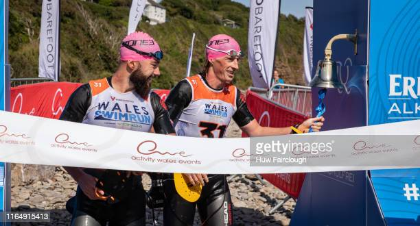 Alexis Charrier and Nicolas Remires finish the race and ring the bell to signify finishing the race in the Wales SwimRun race through Pembrokeshire...