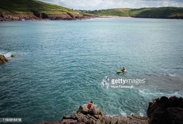 Alexis Charrier and Nicolas Remires swim from the cliff towards Manobier beach during the Wales SwimRun race through Pembrokeshire starting in...