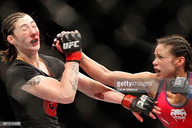 Alexis Dufresne takes a punch from Marion Reneau in their women's bantamweight bout during the UFC 182 event at the MGM Grand Garden Arena on January...