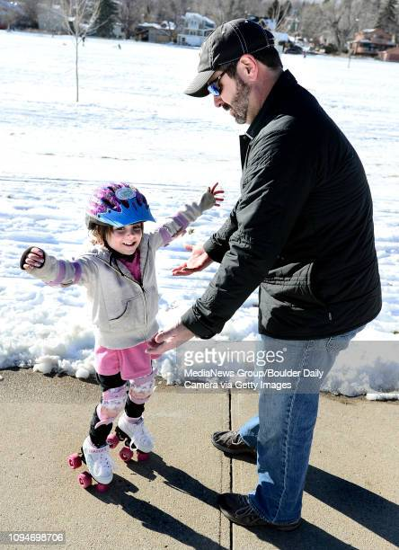 Alexis Faust shows off her balancing skills to her dad Steve and he helps her practice on her new roller skates at North Boulder Park on Sunday...