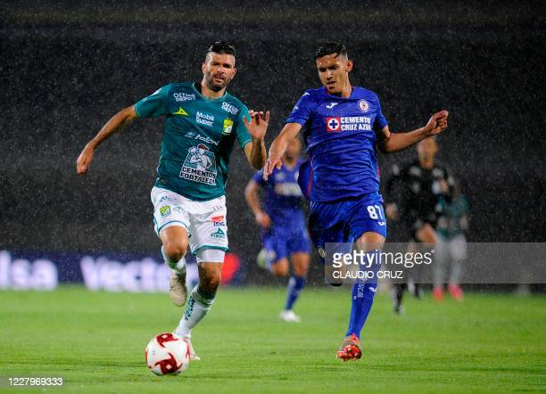 Alexis Gutierrez of Leon and Josue Reyes of Cruz Azul run for the ball during their Mexican Apertura football tournament match at the University...