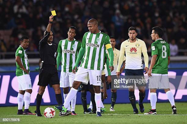Alexis Henriquez of Atletico Nacional is given a yellow card by referee Nawaf Shukralla during the FIFA Club World Cup 3rd place match between Club...