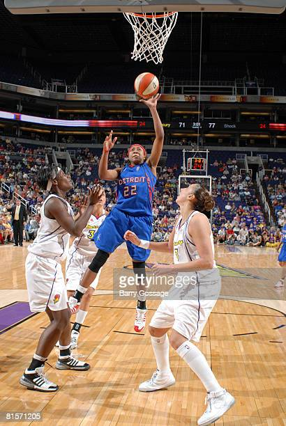 Alexis Hornbuckle of the Detroit Shock shoots against Barbara Farris and Diana Taurasi of the Phoenix Mercury on June 14 at US Airways Center in...